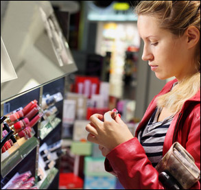 Woman picking out lip ink colors in store